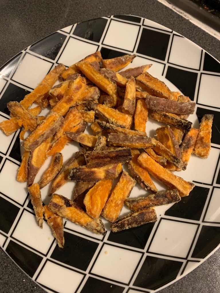 crispy sweet potato fries on a black and white plate